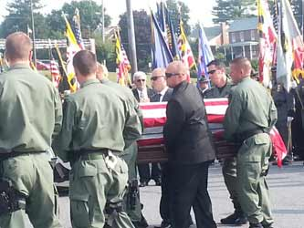 Photo of officers from Tactical Unit carrying POFC Jason Schneider's casket.