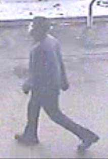 Surveillance photo of suspect two wearing dark clothing.