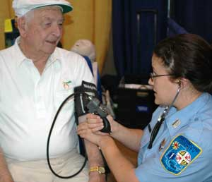 Image of an emergency medical worker preforming a blood pressure check on an senior.