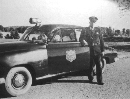 A policeman and what would now be a vintage police car.