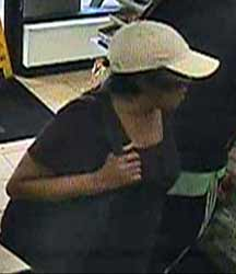 Surveillance photo of female suspect in multiple theft cases.