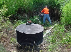 Image of a worker conducting stormwater facility maintenance.
