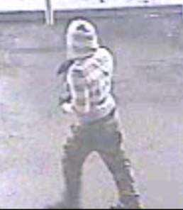 Surveillance photo of suspect one in gray and white striped shirt.