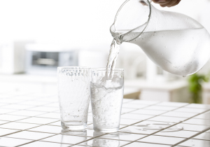 Photo of two glasses on the counter being filled with water